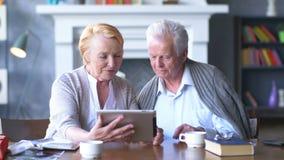 Coppie senior che websurfing su Internet con la compressa Uomo e donna anziani felici che per mezzo del computer della compressa stock footage