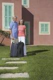 Coppie senior con bagagli in Front Of House Immagini Stock