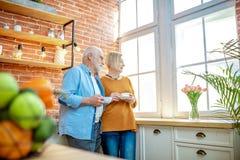 Coppie senior con caffè sulla cucina a casa fotografia stock