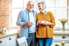 Coppie senior con caffè vicino alla finestra a casa fotografie stock libere da diritti