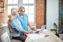 Coppie senior con il computer portatile a casa immagine stock