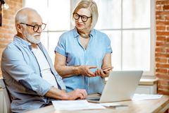Coppie senior con il computer portatile a casa fotografie stock libere da diritti