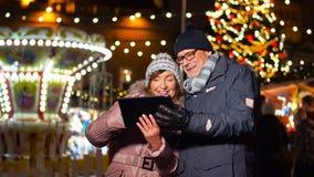 Coppie senior con il pc della compressa al mercato di natale video d archivio