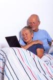 Coppie senior con la compressa ed il giornale a letto Fotografie Stock