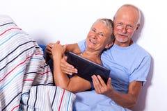 Coppie senior con la compressa ed il giornale a letto Immagine Stock Libera da Diritti