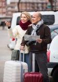 Coppie senior con la mappa ed i bagagli Immagini Stock
