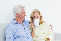 Coppie senior con la tazza di caffè che si siede sul sofà fotografia stock