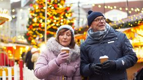 Coppie senior con le bevande calde al mercato di natale archivi video
