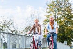 Coppie senior con le biciclette sul ponte Immagini Stock