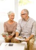 Coppie senior con soldi ed il calcolatore a casa Fotografia Stock