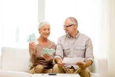 Coppie senior con soldi ed il calcolatore a casa Immagine Stock
