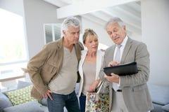 Coppie senior d'avanguardia con l'agente immobiliare che visita nuova casa Immagini Stock