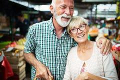 Coppie senior della famiglia che scelgono la bio- frutta e verdura dell'alimento sul mercato durante l'acquisto settimanale fotografia stock libera da diritti