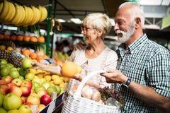 Coppie senior della famiglia che scelgono la bio- frutta e verdura dell'alimento sul mercato durante l'acquisto settimanale immagine stock libera da diritti