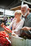 Coppie senior della famiglia che scelgono la bio- frutta e verdura dell'alimento sul mercato durante l'acquisto settimanale fotografia stock