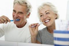 Coppie senior in denti di spazzolatura del bagno fotografie stock libere da diritti
