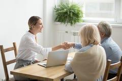 Coppie senior di handshake finanziario del consulente o dell'avvocato sorridente a fotografia stock libera da diritti