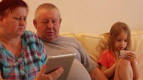 Coppie senior ed i loro grandi bambini che utilizzano compressa digitale nel salone stock footage