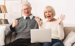 Coppie senior emozionanti che celebrano vittoria, offerta online di conquista dell'asta immagine stock libera da diritti