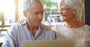 Coppie senior facendo uso del computer portatile in caffè 4k stock footage