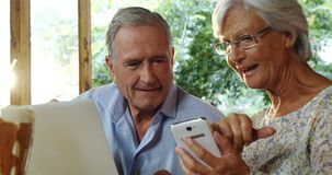 Coppie senior facendo uso del computer portatile e discutere sopra il telefono 4k stock footage