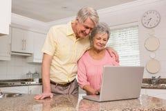 Coppie senior facendo uso del computer portatile insieme Fotografie Stock