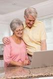 Coppie senior facendo uso del computer portatile insieme Fotografia Stock