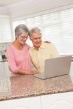 Coppie senior facendo uso del computer portatile insieme Immagini Stock