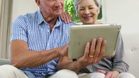 Coppie senior facendo uso della compressa archivi video