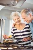 Coppie senior felici che cucinano alimento in cucina Immagini Stock