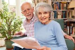 Coppie senior felici che esaminano le finanze a casa immagini stock