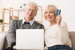 Coppie senior felici che fanno gli acquisti online sul computer portatile immagine stock libera da diritti
