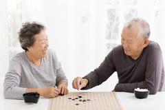 Coppie senior felici che giocano scacchi in salone fotografia stock