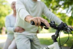 Coppie senior felici che guidano una bicicletta al parco fotografia stock