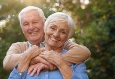 Coppie senior felici che sorridono soddisfatto insieme fuori fotografia stock
