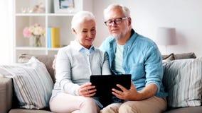 Coppie senior felici con il computer della compressa a casa video d archivio