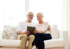 Coppie senior felici con il pc della compressa a casa Immagine Stock