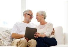 Coppie senior felici con il pc della compressa a casa Fotografie Stock Libere da Diritti