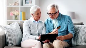 Coppie senior felici con il pc della compressa e la carta di credito stock footage