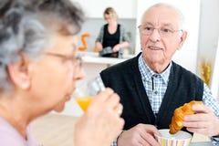Coppie senior felici con il succo d'arancia di vetro Fotografie Stock Libere da Diritti