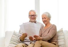 Coppie senior felici con le carte a casa Immagine Stock Libera da Diritti