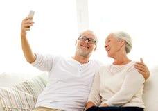 Coppie senior felici con lo smartphone a casa Fotografia Stock