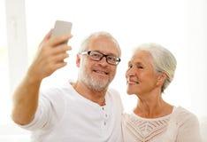 Coppie senior felici con lo smartphone a casa Fotografie Stock Libere da Diritti