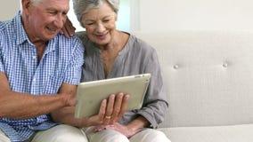 Coppie senior felici facendo uso della compressa archivi video