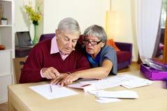 Coppie senior nelle fatture e nelle tasse calcolarici di difficoltà fotografia stock libera da diritti