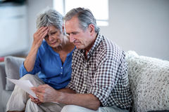 Coppie senior preoccupate che controllano le fatture Immagine Stock