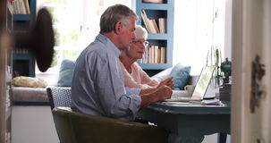 Coppie senior preoccupate in Ministero degli Interni che esamina computer portatile video d archivio