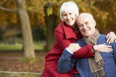 Coppie senior romantiche che si siedono sul recinto In Autumn Woodland Immagine Stock