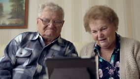 Coppie senior in sofà facendo uso della linguetta elettronica Una coppia senior allegra che ha una video chiacchierata su una com stock footage