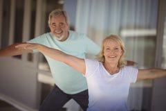 Coppie senior sorridenti che eseguono allungando esercizio Fotografia Stock Libera da Diritti